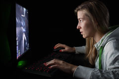 Gamer girl playing a first person shooter Royalty Free Stock Image