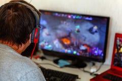 Gamer in headphones using computer stock photo