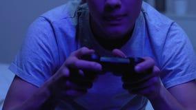 Gamer het spelen videospelletje die bedieningshendel met behulp van bij nacht in plaats van slaap, verslaving stock footage