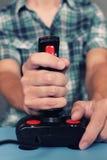 Gamer jouant le jeu vidéo avec la rétro manette Image stock