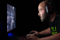 Gamer jouant un premier tireur de personne sur le PC à extrémité élevé Image stock