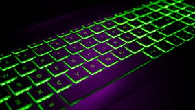 Gamer keyboard Purple and Green backlight. Modern laptop computer royalty free stock image