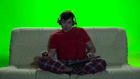 Gamer man many hours spent playing games on the computer. Gamer many hours spent playing games on the computer, sitting at home on large couch, head wearing stock footage