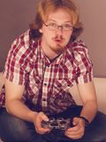 Gamer man playing using gaming pad. Nerd geek young adult man playing on the video console holding game pad. Gaming gamers concept royalty free stock photo