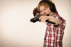 Gamer man shooting from gun. Nerd geek young adult man playing on the video console holding gun wearing headphones with microphone. Gaming gamers concept royalty free stock photography