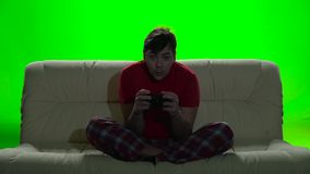 Gamer many hours spent on the couch playing video games. Shadow of the tv falls on the player, sits on bright couch, wearing red t-shirt, with passion plays stock footage