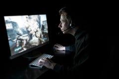 Gamer novo na obscuridade Fotografia de Stock Royalty Free