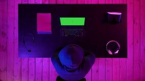 Gamer oder Ausläufer, die ein Spiel auf dem Schirm des Laptops aufpassen Grüne Schirm-Modell-Anzeige stock footage