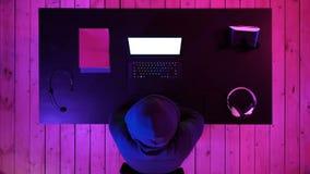 Gamer ou flâmula que olham um jogo na tela do portátil Indicador branco video estoque