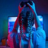 Gamer ou menina da flâmula em casa em uma sala escura com um gamepad, jogando com amigos em linha nos jogos de vídeo com pipoca e imagens de stock royalty free