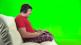 Gamer playing computer games sitting on the sofa. Green screen. Gamer man playing computer games sitting on the sofa sideways to the viewer, head wearing stock video