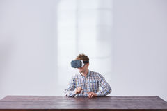 Gamer plays interactive game. Using virtual reality device in white room Royalty Free Stock Image