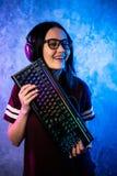 Gamer professionale della ragazza in video gioco di strategia di MMORPG ? lei che posa sopra il fondo blu e rosa variopinto con l fotografia stock libera da diritti