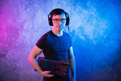 Gamer profissional do menino que guarda o teclado do jogo sobre o rosa colorido e a parede leve de néon azul Conceito dos gamers  foto de stock