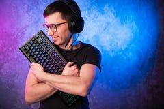 Gamer profissional do menino que guarda o teclado do jogo sobre o rosa colorido e a parede leve de néon azul Conceito dos gamers  imagem de stock