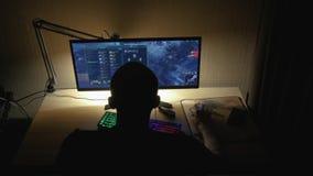 Gamer que joga no jogo de vídeo em linha de MOBA em seu computador pessoal