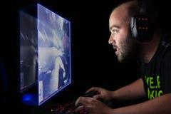 Gamer que joga um primeiro atirador da pessoa no PC da parte alta Fotos de Stock