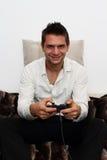 Gamer que se sienta en el sofá con el regulador Imagen de archivo libre de regalías
