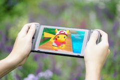 A gamer`s hands holding Nintendo Switch while playing Pokemon Let`s go Pikachu in the garden. royalty free stock photo