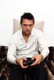 Gamer sitting on couch with controller Royalty Free Stock Image