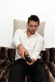 Gamer sitting on couch with controller. And playing Royalty Free Stock Image
