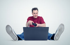 Gamer sitting on the floor playing on laptop Royalty Free Stock Image