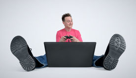 Gamer sitting on the floor playing on laptop Stock Photo