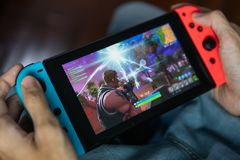 Gamer som spelar den Fortnite leken på den Nintendo strömbrytaren royaltyfria foton