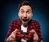 Gamer spielt ein Videospiel mit seinem roten Steuerknüppel lizenzfreies stockbild