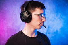 Gamer or streamer in earphones with microphone over colorful pink and blue neon lit wall royalty free stock photo