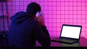 Gamer wearing headset watching stream of a game. White Display. stock image