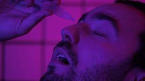 Gamerprogrammerare Hacker Pouring Medicine tappar i hans ?gon arkivfilmer
