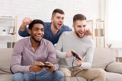 gamers Ευτυχή άτομα που παίζουν τα τηλεοπτικά παιχνίδια στο σπίτι στοκ φωτογραφίες με δικαίωμα ελεύθερης χρήσης