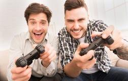 gamers Ευτυχείς τύποι που παίζουν τα τηλεοπτικά παιχνίδια στο σπίτι στοκ φωτογραφία με δικαίωμα ελεύθερης χρήσης