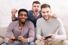 gamers Συγκινημένα άτομα που παίζουν το τηλεοπτικό παιχνίδι στο σπίτι στοκ εικόνες