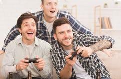 gamers Amigos felices que juegan a los videojuegos en casa fotos de archivo libres de regalías