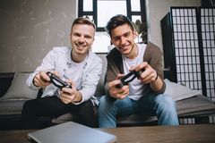 Gamers playing party. Another close up of attractive boys sitting on the couch close to the coffe table and looking straight to the screen. THey are playing Royalty Free Stock Image