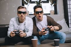 Gamers playing party. Close up of friends that are fond of playing. For playing game they are using gamepads and special glasses. Boys enjoy the game and want to Stock Photo