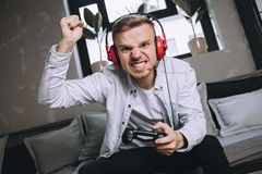 Gamers playing party. Passionate and attractive gamer has won a competition. The game was really hard so young man can`t keep his emotions inside of him. He Royalty Free Stock Images