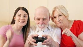 Gamers senior della figlia e delle coppie che giocano video gioco a casa Famiglia felice che gode insieme del tempo video d archivio
