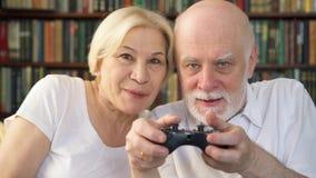 Gamers superiores dos pares que jogam o jogo de vídeo em casa Jogadores com o controlador remoto do console do jogo video estoque