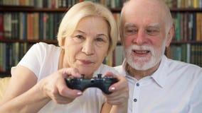 Gamers superiores dos pares que jogam o jogo de vídeo em casa Jogadores com o controlador remoto do console do jogo filme