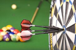 Games. Darts in a dart board with a pool game in the background(shallow dof royalty free stock photography