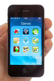 Games on an Apple iPhone 4s. BATH, UK - JANUARY 17, 2014: A hand holding an Apple iPhone 4s which is displaying a selection of well known games including the Stock Image