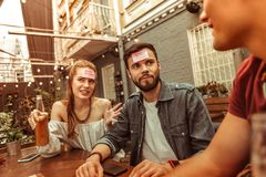 Confused mates spending time at the bar playing hedbanz game. Games at the bar. Confused attractive cheerful good-looking active vigorous mates spending time at stock photography