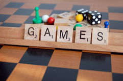 Games. Board game pieces and the word games written in scrabble letters Royalty Free Stock Photos