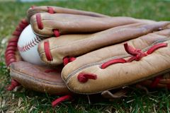 Between games. Close up of baseball and glove with unique red lacing Stock Photo