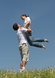 Games on fresh air 2. Man holds the girl on hands standing on a green grass on a background of the blue sky Stock Images