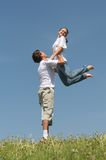 Games on fresh air. Man holds the girl on hands standing on a green grass on a background of the blue sky Stock Photos
