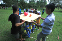 Games hone the cooperation of children and parents. Parents and children play a compact game put the ball in Solo, Central Java, Indonesia. The game is to hone Royalty Free Stock Photo